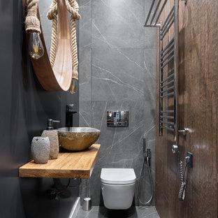 Пример оригинального дизайна: туалет в современном стиле с инсталляцией, коричневой плиткой, серой плиткой, настольной раковиной, серым полом, серыми стенами, столешницей из дерева и коричневой столешницей