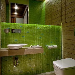 Пример оригинального дизайна: маленький туалет в современном стиле с инсталляцией, зеленой плиткой, плиткой мозаикой, настольной раковиной, светлым паркетным полом, столешницей из дерева, бежевым полом и бежевой столешницей