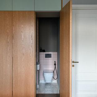 Diseño de aseo minimalista, de tamaño medio, con sanitario de pared, baldosas y/o azulejos rosa, paredes grises, suelo de terrazo y suelo gris