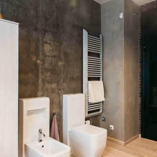 Cette image montre un WC et toilettes urbain avec un placard à porte plane, des portes de placard blanches, un bidet, un mur gris, un sol en bois clair et un sol beige.