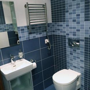 На фото: туалет среднего размера в современном стиле с стеклянными фасадами, инсталляцией, синей плиткой, керамической плиткой, разноцветными стенами, полом из керамогранита, подвесной раковиной и синим полом с