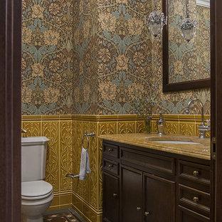 На фото: туалет в викторианском стиле с фасадами с утопленной филенкой, темными деревянными фасадами, раздельным унитазом, разноцветными стенами, разноцветным полом и желтой столешницей