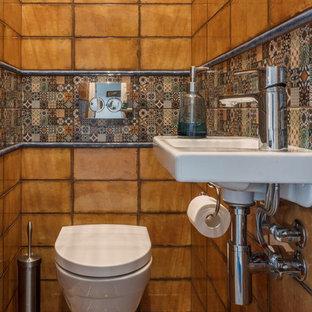 Новый формат декора квартиры: маленький туалет в стиле фьюжн с инсталляцией, оранжевой плиткой, керамической плиткой, полом из керамической плитки, подвесной раковиной и разноцветным полом
