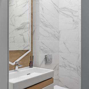 Пример оригинального дизайна: маленький туалет в современном стиле с плоскими фасадами, белыми фасадами, инсталляцией, серой плиткой, керамогранитной плиткой, монолитной раковиной, бежевым полом и белой столешницей