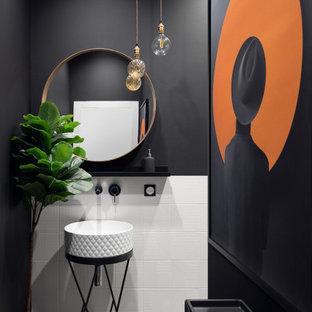 На фото: туалет среднего размера в современном стиле с фасадами островного типа, белой плиткой, керамогранитной плиткой, черными стенами, настольной раковиной, бежевым полом и напольной тумбой с