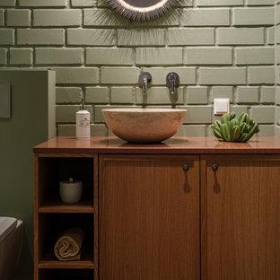 На фото: туалет в современном стиле с фасадами цвета дерева среднего тона, зелеными стенами, настольной раковиной, коричневой столешницей, фасадами с утопленной филенкой, зеленой плиткой, столешницей из дерева и зеленым полом с