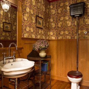 Foto di un bagno di servizio vittoriano di medie dimensioni con lavabo sospeso, WC a due pezzi, pareti marroni, pavimento in legno massello medio e pavimento arancione