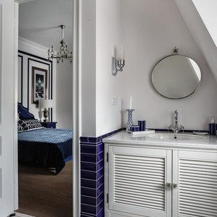 Cette image montre un petit WC et toilettes traditionnel avec des portes de placard blanches, un carrelage de pierre, un mur blanc, un sol en carrelage de céramique, un plan de toilette en surface solide, un sol multicolore, un placard à porte persienne, un carrelage bleu et un lavabo encastré.