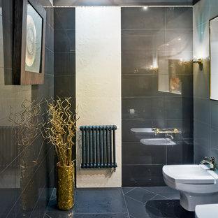 Cette image montre un grand WC et toilettes design avec des carreaux de céramique, un mur noir, un sol en carrelage de céramique et un sol gris.