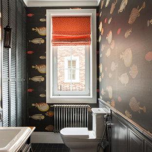 Esempio di un bagno di servizio classico con WC a due pezzi, lavabo da incasso, pavimento nero, ante con finitura invecchiata, pareti multicolore, boiserie e carta da parati