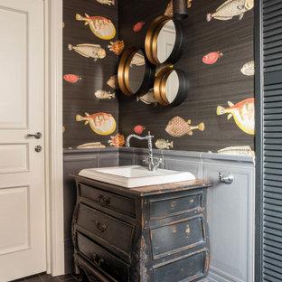 На фото: туалет в стиле современная классика с накладной раковиной, черным полом, искусственно-состаренными фасадами, разноцветными стенами, напольной тумбой, панелями на стенах и обоями на стенах