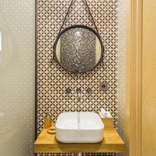 Стильный дизайн: туалет в современном стиле с бежевой плиткой, настольной раковиной, столешницей из дерева и коричневой столешницей - последний тренд