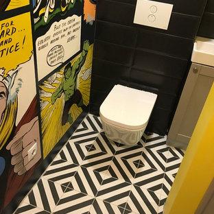 Ispirazione per un piccolo bagno di servizio industriale con ante con riquadro incassato, ante grigie, WC sospeso, piastrelle nere, piastrelle in ceramica, pareti multicolore, pavimento in gres porcellanato, lavabo sospeso e pavimento nero