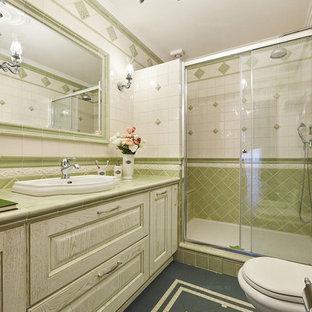 На фото: туалет среднего размера в классическом стиле с фасадами с выступающей филенкой, искусственно-состаренными фасадами, раздельным унитазом, белой плиткой, керамической плиткой, зелеными стенами, полом из керамической плитки, накладной раковиной, столешницей из плитки, зеленым полом и зеленой столешницей с