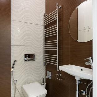 На фото: туалет в современном стиле с инсталляцией, белой плиткой, коричневой плиткой и подвесной раковиной с