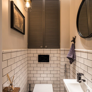 Cette photo montre un WC et toilettes industriel avec un WC suspendu, un carrelage blanc, un mur beige, un lavabo suspendu et un sol gris.
