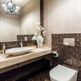 На фото: туалеты в современном стиле с инсталляцией, коричневой плиткой, плиткой мозаикой, бежевыми стенами, мраморным полом, настольной раковиной и коричневым полом