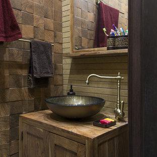 Foto de aseo campestre con armarios estilo shaker, puertas de armario de madera oscura, baldosas y/o azulejos marrones, lavabo sobreencimera, encimera de madera y encimeras marrones