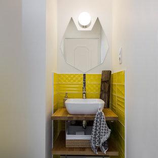 Свежая идея для дизайна: маленький туалет в скандинавском стиле с открытыми фасадами, желтой плиткой, белыми стенами, столешницей из дерева, серым полом, настольной раковиной и коричневой столешницей - отличное фото интерьера