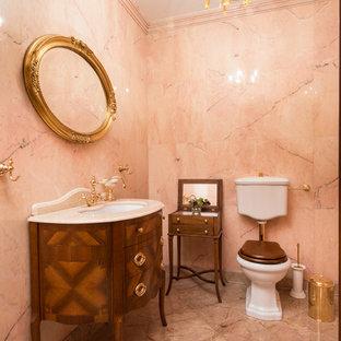 Неиссякаемый источник вдохновения для домашнего уюта: туалет среднего размера в классическом стиле с розовой плиткой, каменной плиткой, мраморным полом, фасадами цвета дерева среднего тона, раздельным унитазом, врезной раковиной и бежевым полом