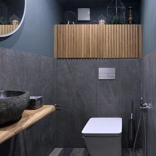 Стильный дизайн: туалет в современном стиле с инсталляцией, керамогранитной плиткой, полом из керамогранита, настольной раковиной, серой плиткой, серыми стенами, столешницей из дерева и разноцветным полом - последний тренд