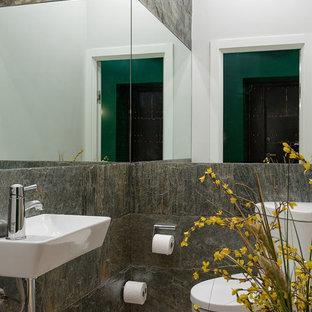 Cette photo montre un petit WC et toilettes tendance avec un WC séparé, un mur gris, un lavabo suspendu, un carrelage gris et un carrelage de pierre.