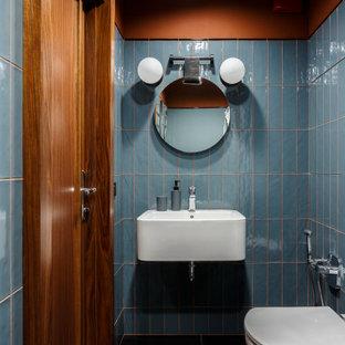 Réalisation d'un WC et toilettes design avec un carrelage bleu, un mur bleu, un lavabo suspendu et un sol noir.