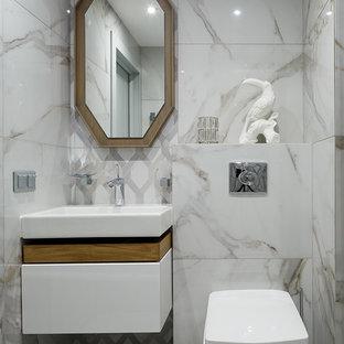На фото: со средним бюджетом туалеты среднего размера в современном стиле с инсталляцией, плоскими фасадами, белыми фасадами, белой плиткой, белыми стенами, консольной раковиной и белым полом