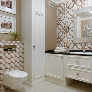 Design ideas for a traditional cloakroom in Moscow with recessed-panel cabinets, a wall mounted toilet, mosaic tiles, a built-in sink, beige floors, black worktops, beige cabinets, multi-coloured tiles and brown walls.