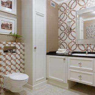 На фото: туалеты в стиле современная классика с фасадами с утопленной филенкой, инсталляцией, плиткой мозаикой, накладной раковиной, бежевым полом, черной столешницей, бежевыми фасадами, разноцветной плиткой и коричневыми стенами