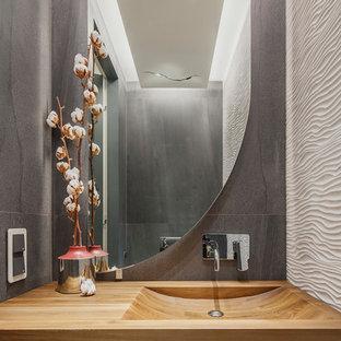 Пример оригинального дизайна: маленький туалет в современном стиле с плоскими фасадами, серыми фасадами, белой плиткой, серой плиткой, керамической плиткой, столешницей из дерева, монолитной раковиной и коричневой столешницей
