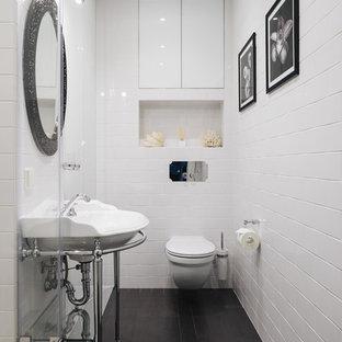 Свежая идея для дизайна: туалет в стиле неоклассика (современная классика) с инсталляцией, белой плиткой, консольной раковиной, черным полом и правильным освещением - отличное фото интерьера