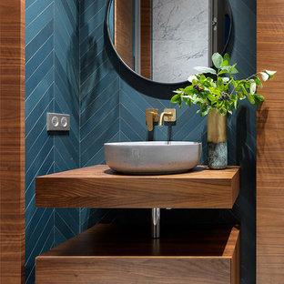 Пример оригинального дизайна: туалет в современном стиле с плоскими фасадами, фасадами цвета дерева среднего тона, мраморным полом, настольной раковиной, столешницей из дерева, белым полом и коричневой столешницей