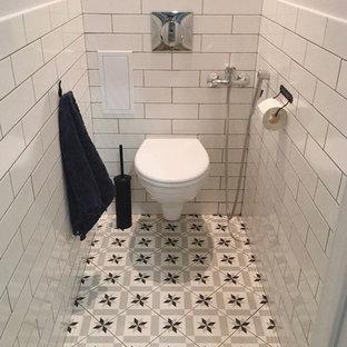 Неиссякаемый источник вдохновения для домашнего уюта: туалет в скандинавском стиле с керамической плиткой, белыми стенами, полом из керамической плитки и серым полом