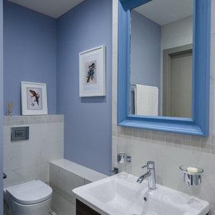 Пример оригинального дизайна интерьера: туалет в стиле современная классика с плоскими фасадами, фасадами цвета темного дерева, инсталляцией, белой плиткой, синими стенами, монолитной раковиной и серым полом