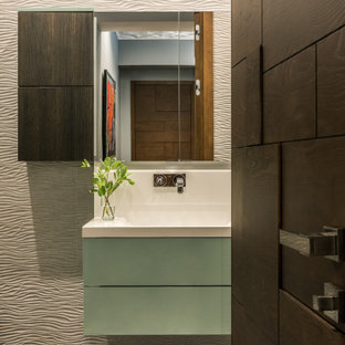 Small contemporary powder room in Moscow with turquoise cabinets, a wall-mount toilet, beige tile, porcelain tile, beige walls, ceramic floors, a wall-mount sink, solid surface benchtops, multi-coloured floor and white benchtops.