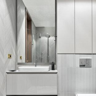 Источник вдохновения для домашнего уюта: туалет в современном стиле с плоскими фасадами, белыми фасадами, инсталляцией, настольной раковиной, белой столешницей и встроенной тумбой