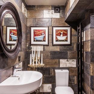Идея дизайна: туалет в стиле рустика с коричневой плиткой, подвесной раковиной, коричневым полом, раздельным унитазом и разноцветными стенами