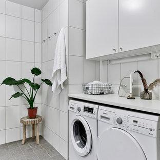 Foto på en mellanstor minimalistisk linjär tvättstuga, med släta luckor, vita skåp, en tvättmaskin och torktumlare bredvid varandra, vita väggar och klinkergolv i keramik