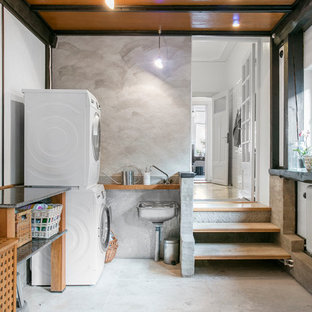This is an example of a large scandinavian l-shaped utility room in Malmo with open cabinets, white walls, concrete flooring, a stacked washer and dryer and an utility sink.