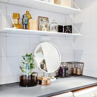 Foto di un ripostiglio-lavanderia nordico con nessun'anta, top in cemento, pareti bianche e lavatrice e asciugatrice nascoste