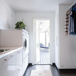 Idéer för funkis parallella tvättstugor, med en nedsänkt diskho, släta luckor, vita skåp, vita väggar, en tvättmaskin och torktumlare bredvid varandra och svart golv