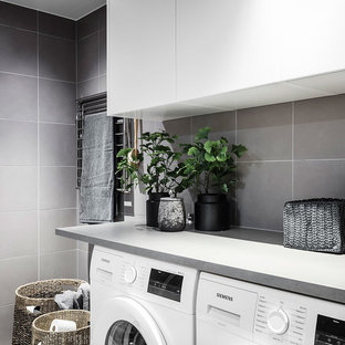 Photo of a large scandi utility room in Gothenburg with flat-panel cabinets, white cabinets, white walls, light hardwood flooring, a side by side washer and dryer and grey floors.