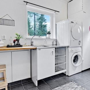 Inredning av en minimalistisk mellanstor linjär tvättstuga, med släta luckor, vita skåp, träbänkskiva, vita väggar, en tvättpelare, grått golv och en integrerad diskho