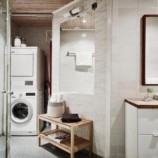 Exempel på en nordisk tvättstuga, med släta luckor, vita skåp, vita väggar, träbänkskiva och klinkergolv i porslin