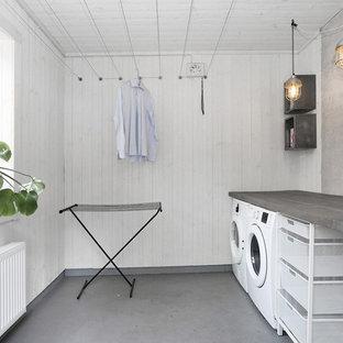 Diseño de cuarto de lavado lineal, nórdico, con fregadero de un seno, armarios abiertos, paredes blancas, lavadora y secadora juntas y suelo gris
