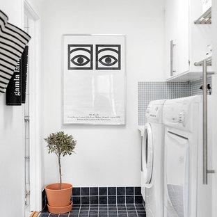 Foto på ett mellanstort nordiskt linjärt grovkök, med släta luckor, vita skåp, vita väggar, klinkergolv i porslin och en tvättmaskin och torktumlare bredvid varandra