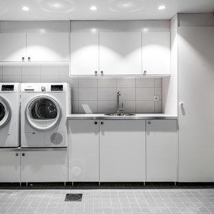 Idéer för en mellanstor modern tvättstuga, med släta luckor, vita skåp och vita väggar
