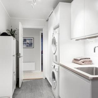 На фото: линейные прачечные в скандинавском стиле с одинарной раковиной, плоскими фасадами, белыми фасадами, белыми стенами, с сушильной машиной на стиральной машине и серым полом