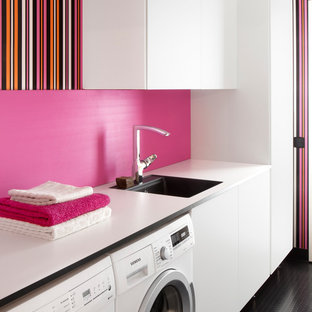 Inspiration for a mid-sized contemporary single-wall dedicated laundry room in Orebro with a single-bowl sink, flat-panel cabinets, white cabinets, pink walls, a side-by-side washer and dryer, laminate benchtops and black floor.